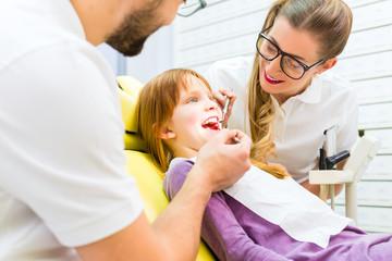 Zahnärzt behandelt Mädchen in Zahnarztpraxis
