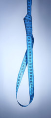 Tape measure noose on blue background - diet concept