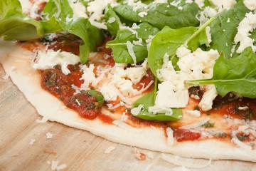 Spinatpizza auf Holzbrett