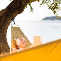 Lady reading book in hammock.