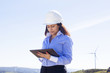 Female engineer working with a tablet at wind farm - 64544948