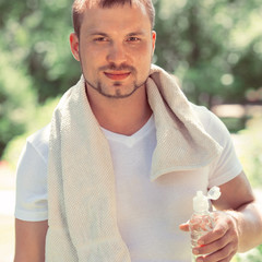 Young sexy male athlete is refreshing himself with water