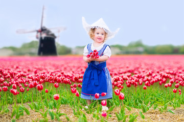 Pretty girl in Dutch costume in tulips field with windmill