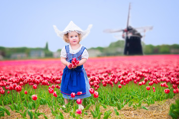 Girl in national Dutch costume in tulips field with windmill