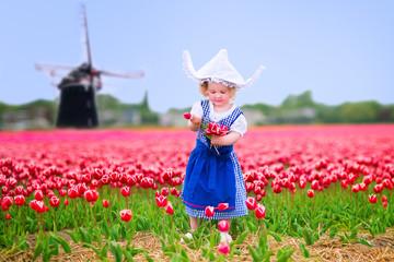 Girl in national Dutch costume in tulips field next windmill