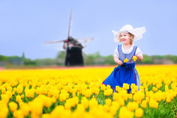 Adorable girl in Dutch costume in tulips field next windmill