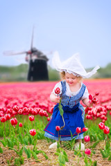 Sweet girl in Dutch costume in tulips field next windmill