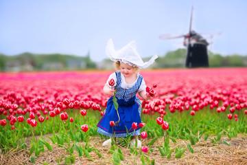 Pretty girl in Dutch costume in tulips field next windmill