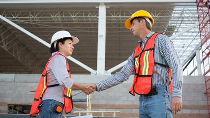 Male and Female Workers Shake Hands