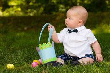 Cute infant baby boy playing with Easter eggs and basket