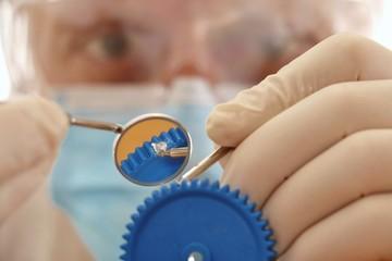 zanarzt repariert zahnrad mit dentalbesteck und plombenstopfer