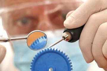 zanarzt repariert zahnrad mit dentalbesteck und bohrer