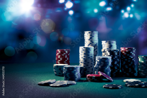 Casino chips with dramatic lighting and lens flares - 64553710