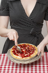 Woman holding round strawberry cake over kitchen table