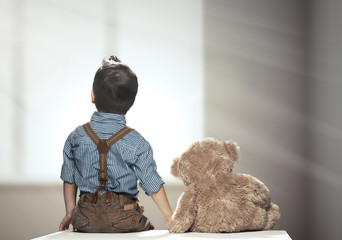 Rear view of small boy with bear