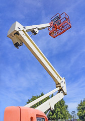 Cherry picker or boom lift reaching high up,sky and clouds