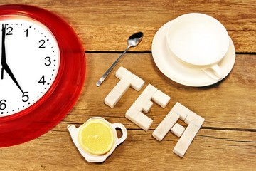 Tea cup, clock and sign made from sugar on brown wooden table