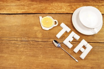 Tea cup and sign made from sugar on brown wooden table