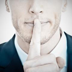 Top Secret - Geschäftsmann mit Finger vor Mund