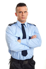 Portrait of young strict man standing in police uniform