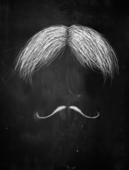 Hair and curly mustache on blackboard