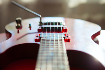 Red electric guitar laying on a red velvet.