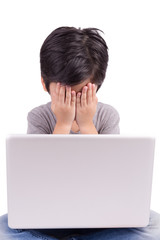 Little boy in front of laptop hiding his face