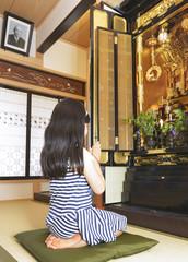 仏壇に手を合わせる女の子