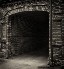 Entrance tunnel of old brick. Dark arch. Black white.