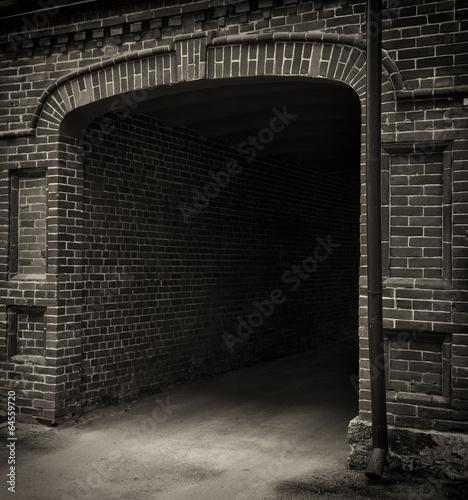 Entrance tunnel of old brick. Dark arch. Black white. - 64559720