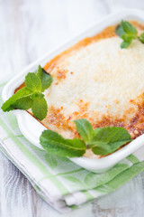 Close-up of vegetable lasagna with mint leaves, vertical shot