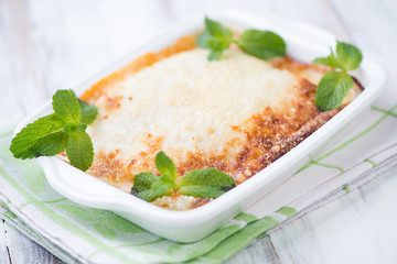 Vegetable lasagna decorated with mint leaves, horizontal shot