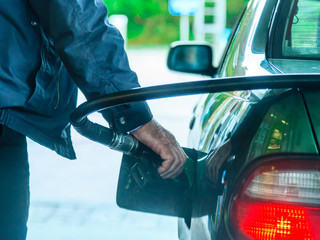 Car refuel fueling at the filling station, holding a fuel pump