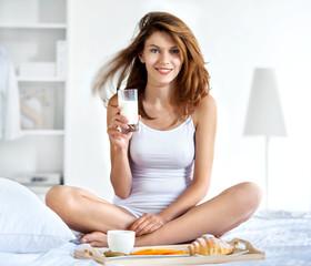 Natural smiling brunette holding glass of milk in bright bedroom