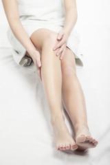 Junge Frau cremt Beine ein