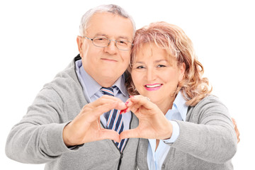 Mature couple making heart with their hands