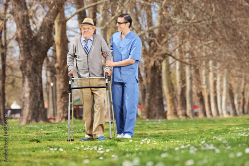 Medical professional helping a senior in park