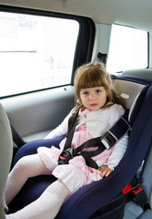 little cute girl sitting in the car in child safety seat and smi