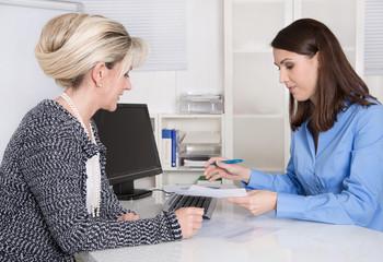 Zwei weibliche Personen in einem Gespräch im Büro