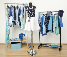 Closet with blue clothes on hangers.Summer outfit on mannequin.