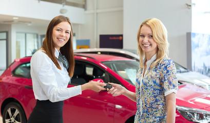 Happy saleswoman handing over car keys