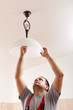 Man screwing a new lightbulb into ceiling lamp