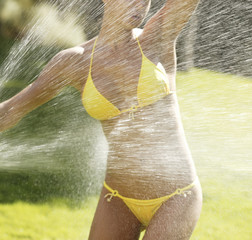 Spray water on a female body with bikini