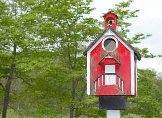 Well used rustic red birdhouse