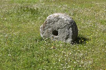 Alter Mühlstein in einem Klostergarten