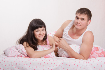 Young girl and the guy put up, lying in bed
