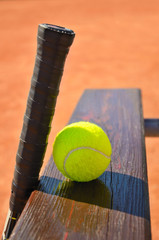 tennis racket and ball on the bench