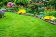 Leinwandbild Motiv Rasenfläche mit Garten im Hintergrund