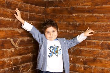 Мальчик стоит подняв руки вверх и смотрит в камеру