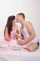 Young couple kissing and eat chocolate in bed